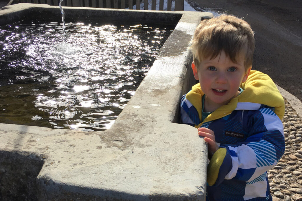 Toddler standing by fountain